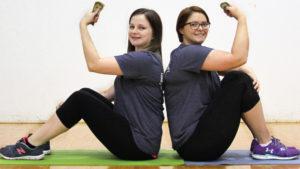 Ladies holding money on yoga mats